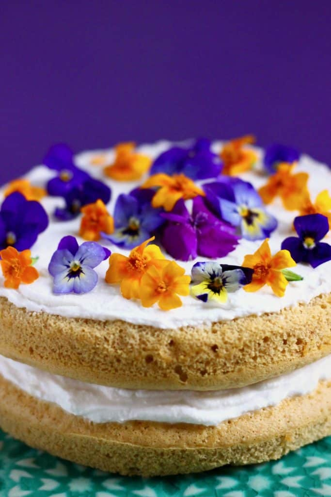 A pumpkin sponge sandwiched with white frosting topped with purple and orange flowers on a green cake stand against a purple background