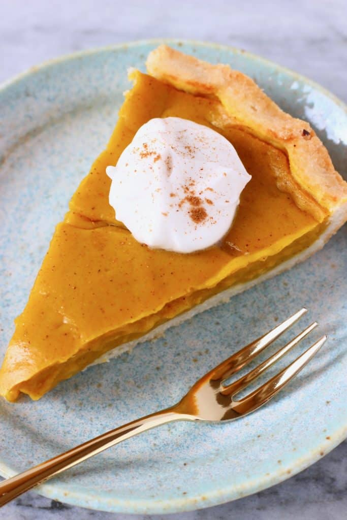 A slice of pumpkin pie topped with cream and sprinkled with cinnamon on a blue plate with a gold fork
