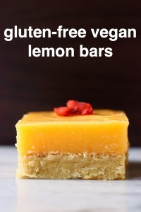 A lemon bar topped with goji berries on a marble slab