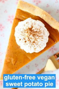 A slice of sweet potato pie topped with white cream on a plate with a gold fork