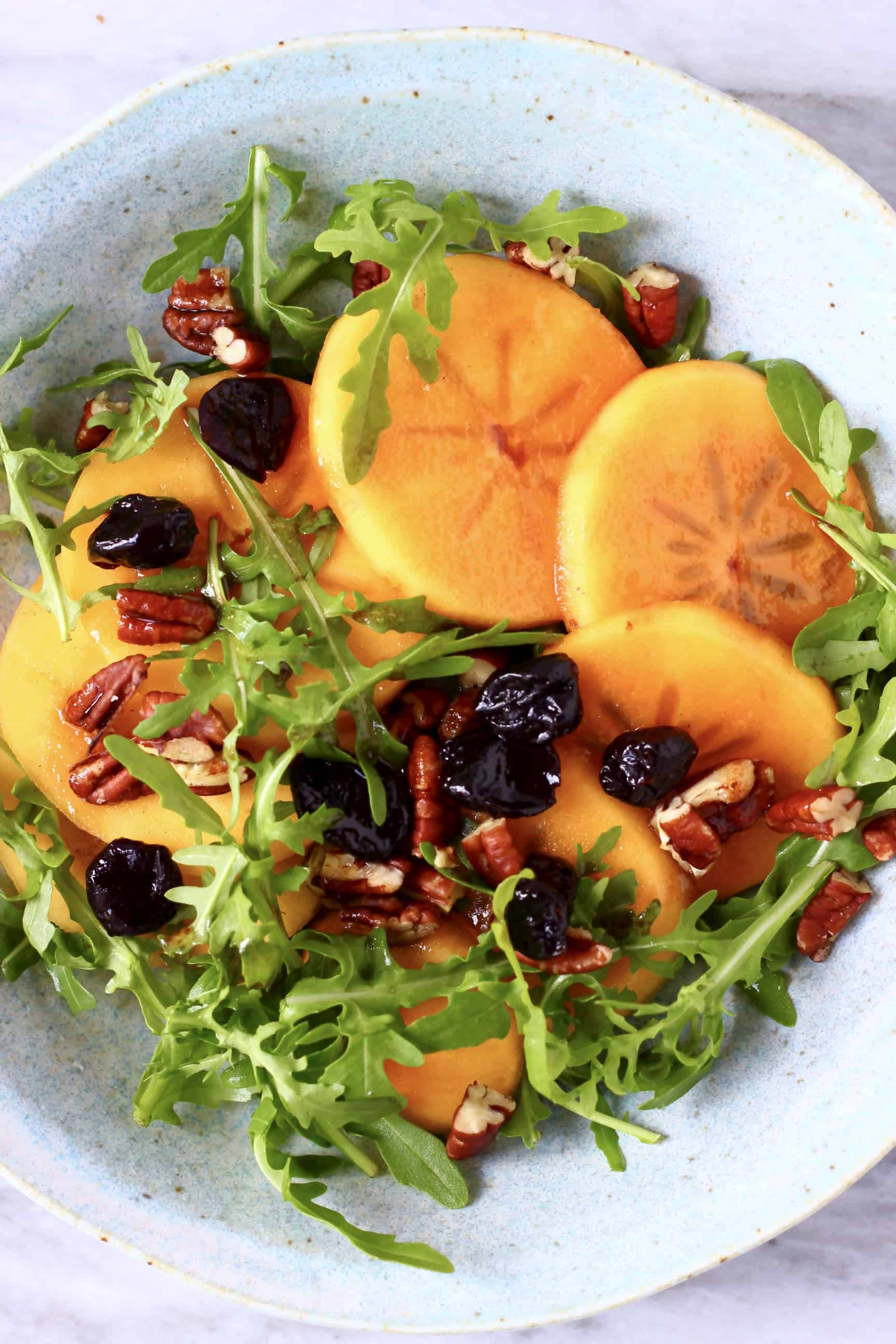 Persimmon salad in a blue bowl against a marble background