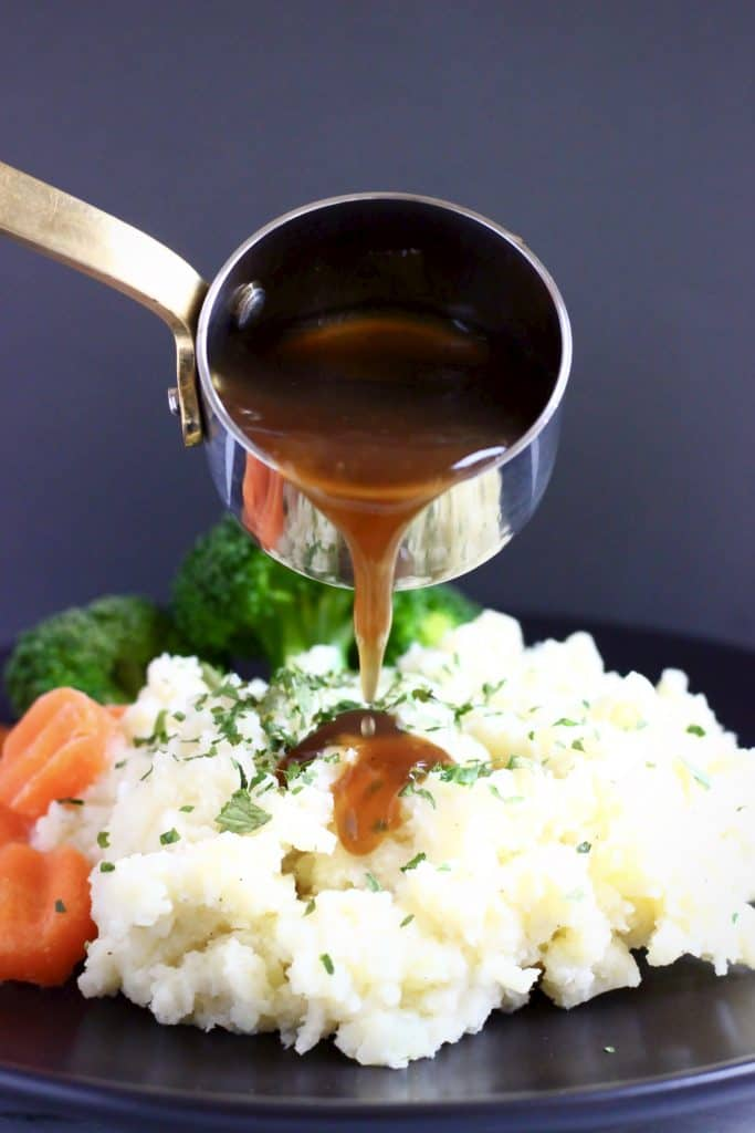 Mashed potatoes topped with green herbs with sliced carrots and broccoli on a black plate with brown gravy being poured over