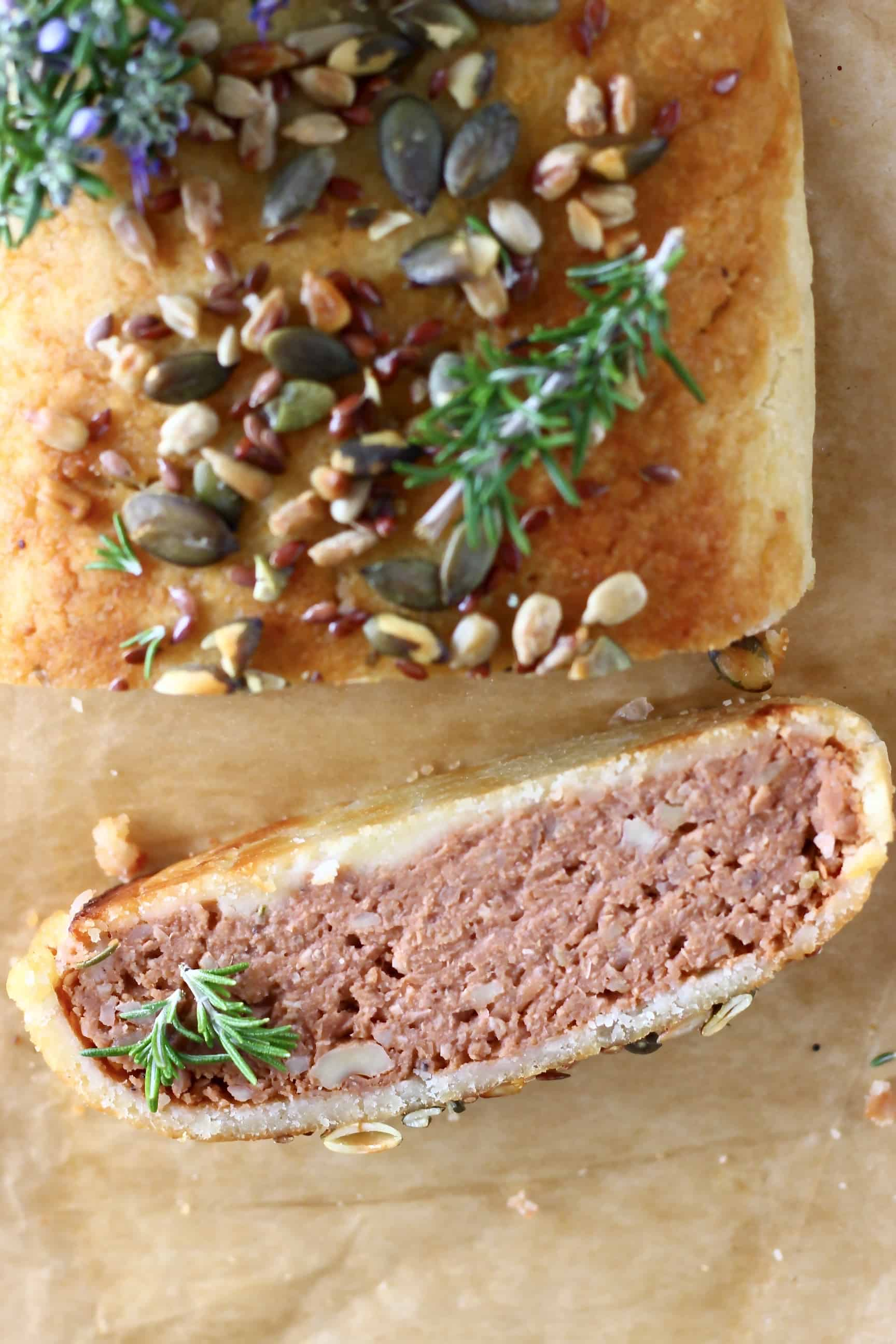 A vegan Wellington topped with mixed seeds with a slice of it on the side on a sheet of brown baking paper