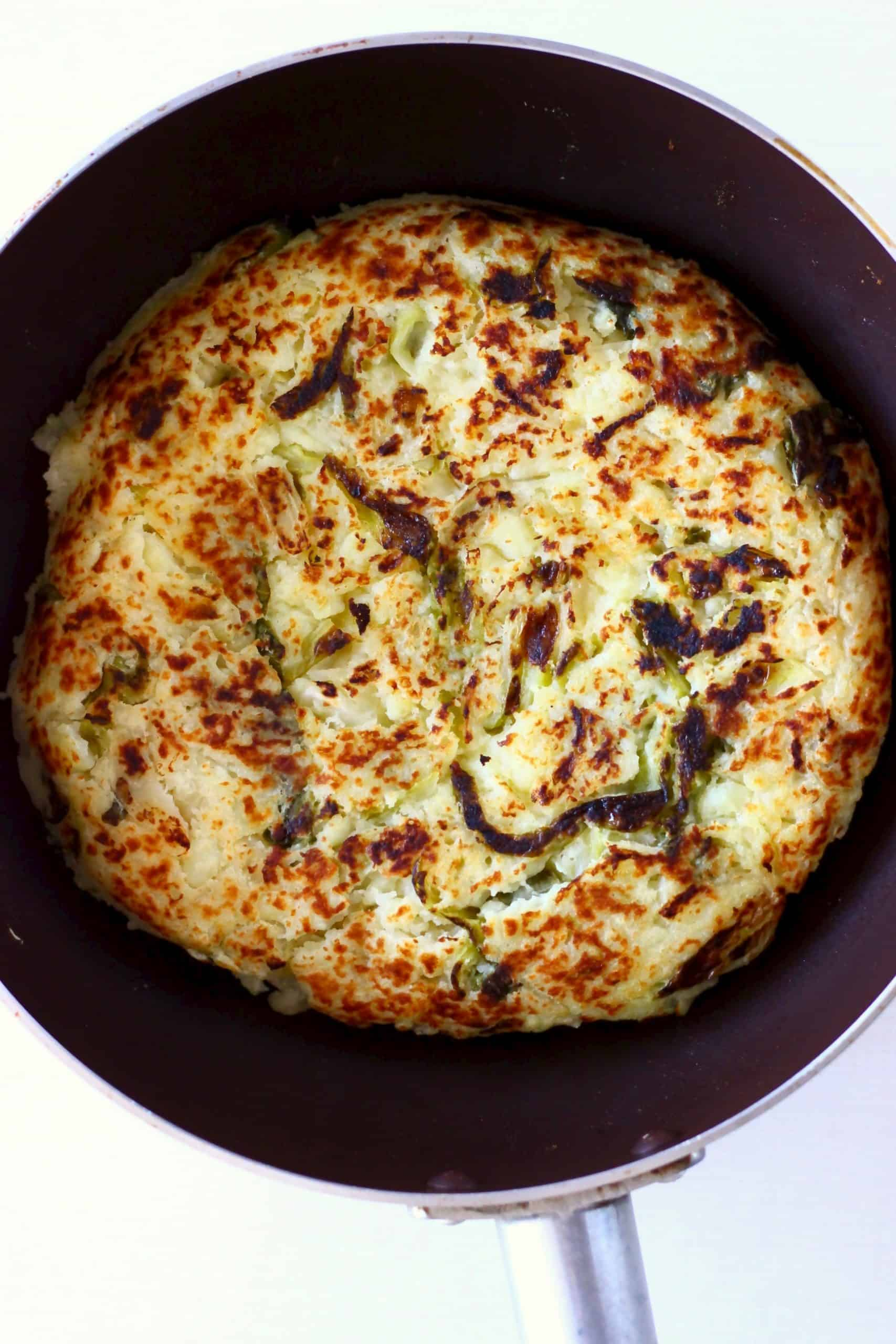 A circular, golden brown bubble and squeak cake in a dark frying pan