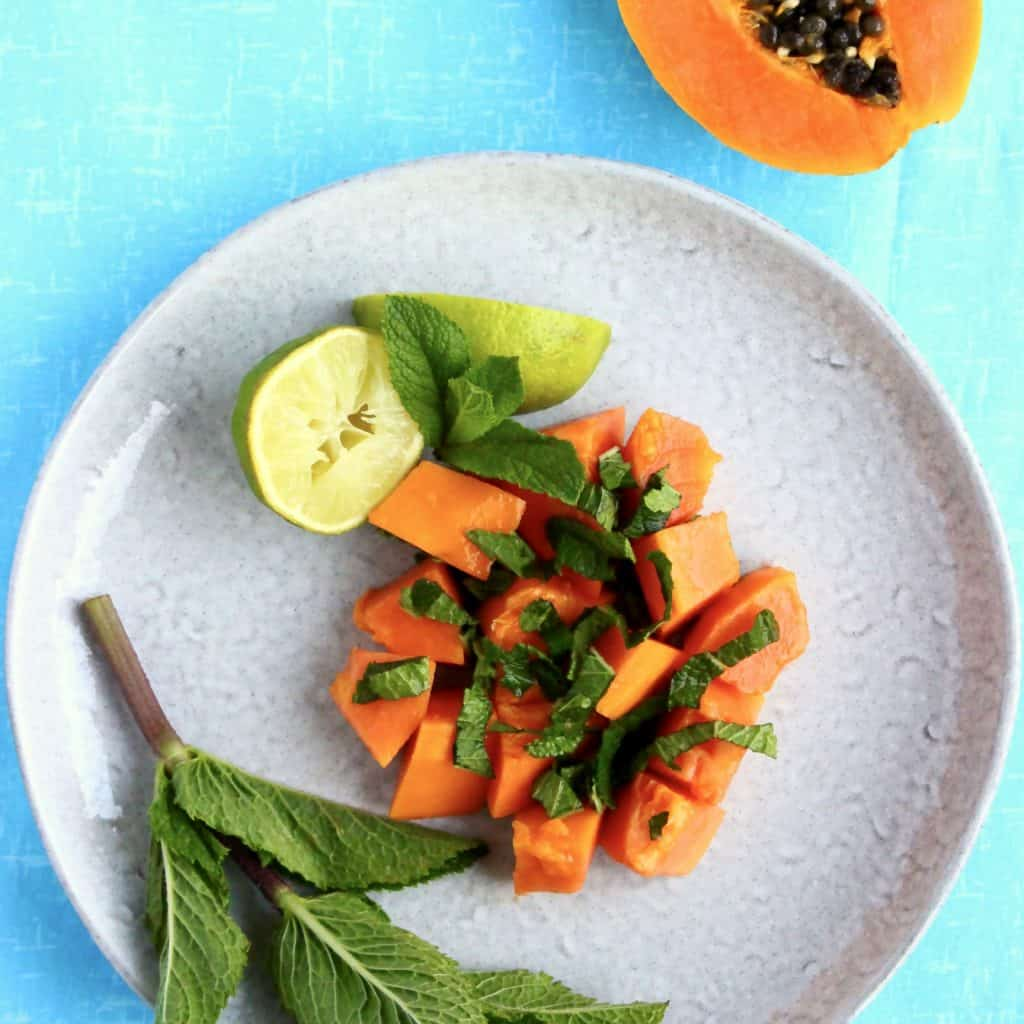 Papaya, lime and mint salad on a grey plate against a blue background