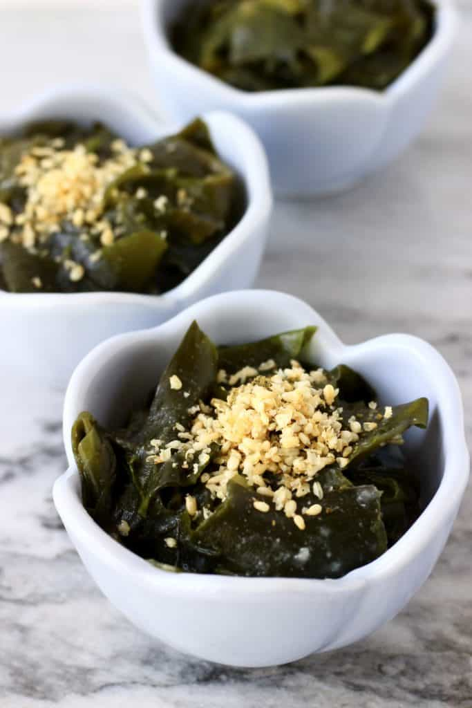 Seaweed salad topped with sesame seeds in three small blue bowls