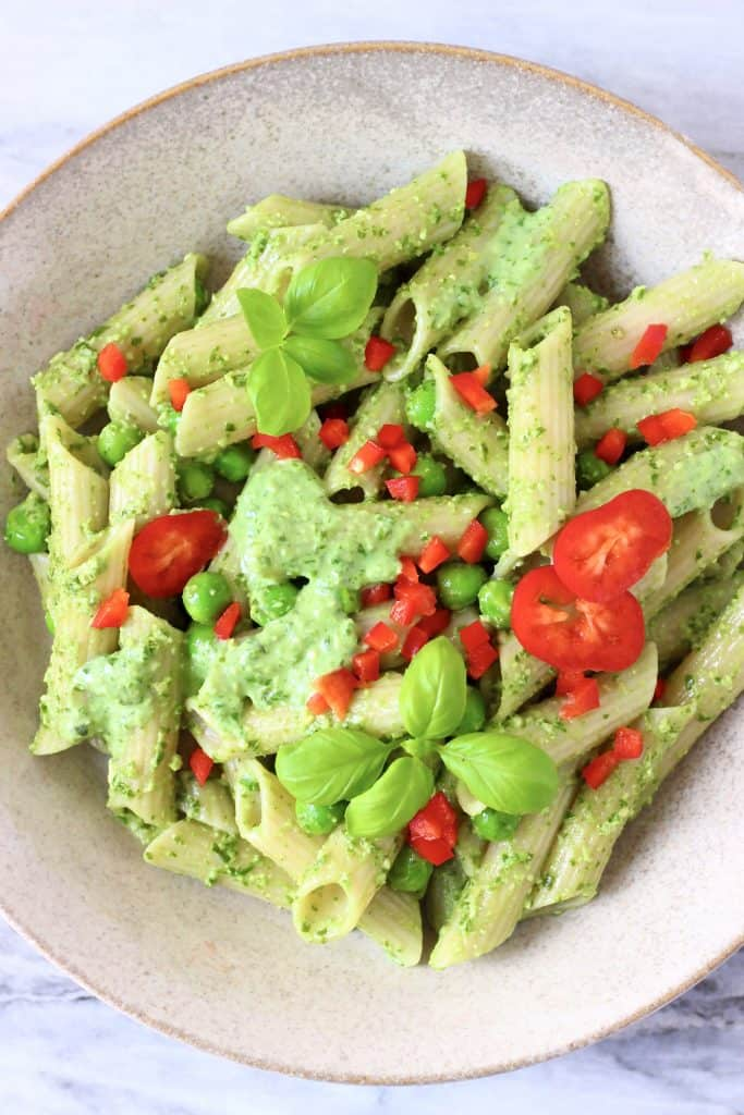 Penne pasta with pesto sauce, green peas and chopped red pepper in a beige bowl
