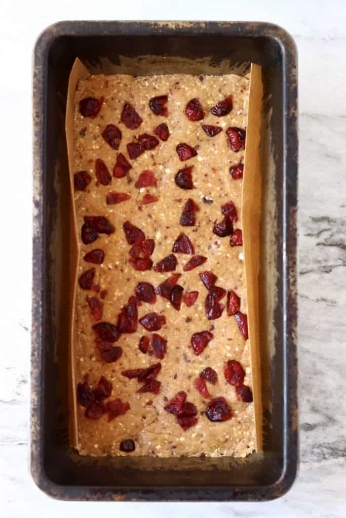 Vegan protein bar mixture topped with dried cranberries in a black loaf tin