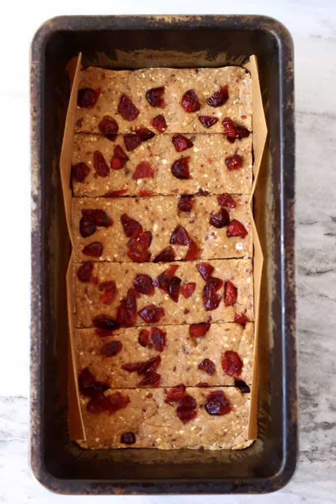 Vegan protein bar mixture topped with dried cranberries in a black loaf tin cut into six bars