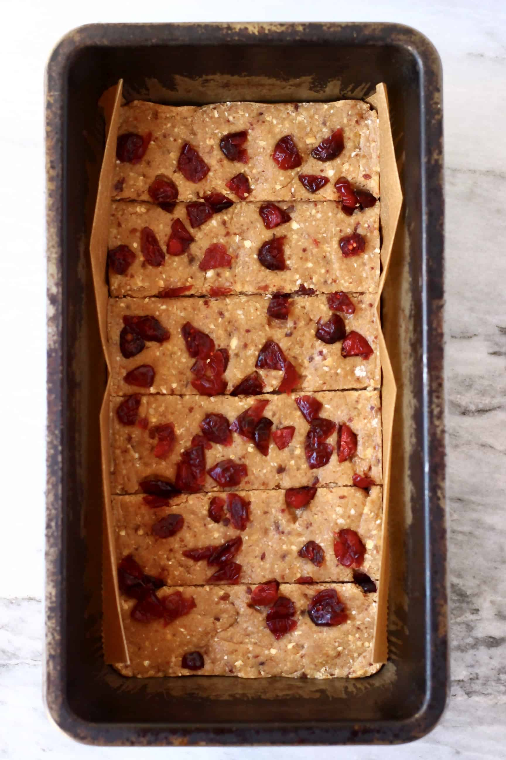Vegan protein bar mixture topped with dried cranberries in a loaf tin cut into six bars