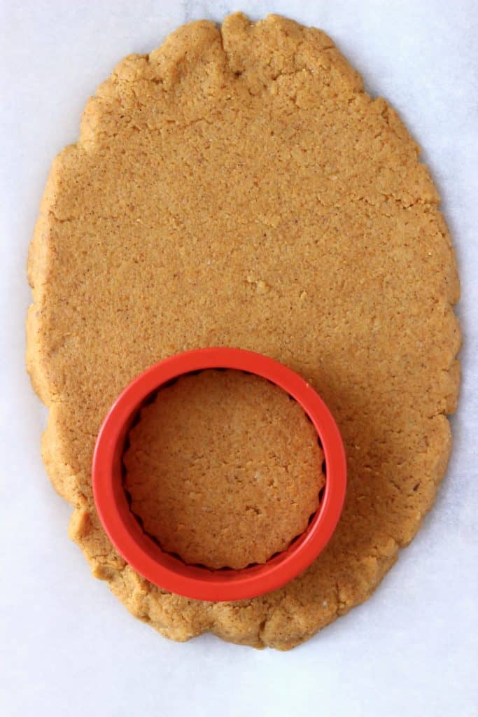 Raw pumpkin cookie dough rolled out on a white baking sheet with a circular cookie cutter
