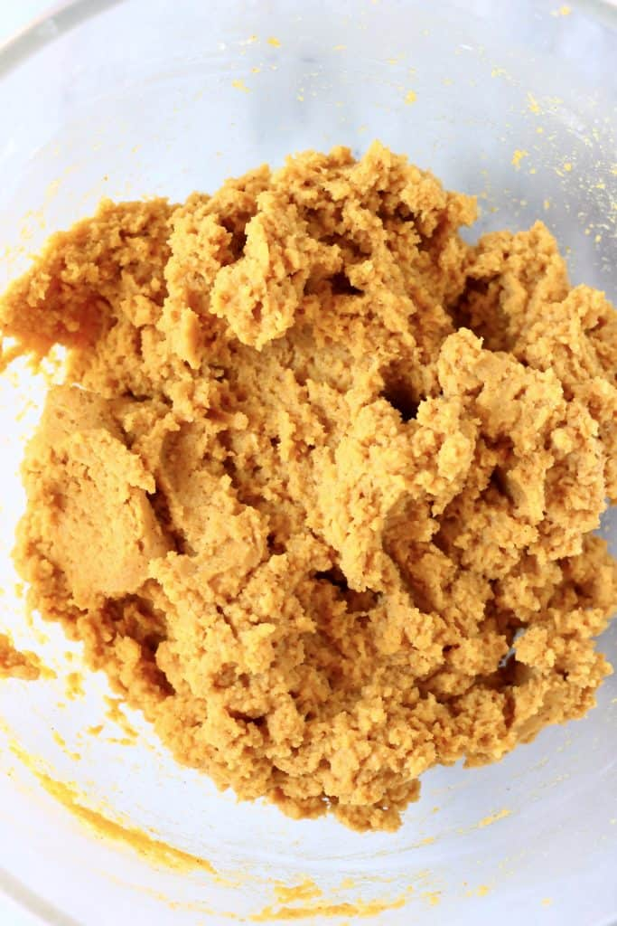 Raw pumpkin scone dough in a glass mixing bowl