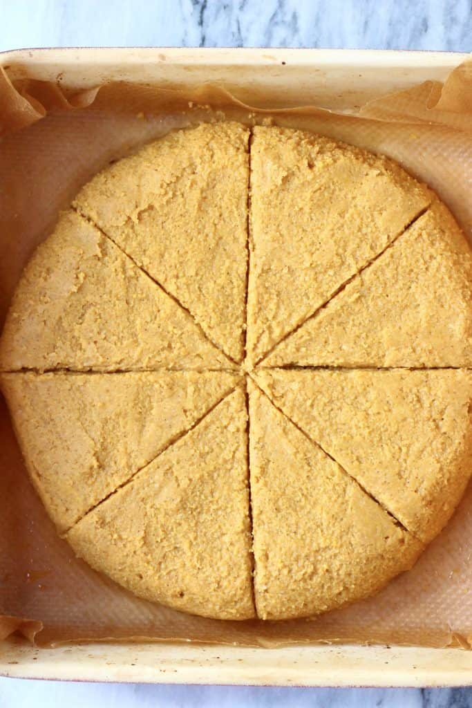 A circle of pumpkin scone dough in a baking tray cut into eight