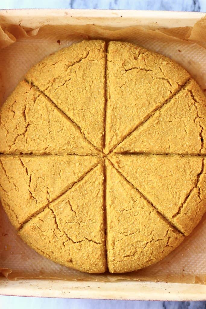 A circle of pumpkin scones in a baking tray cut into eight