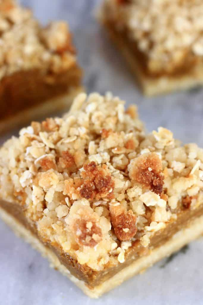 Three vegan pumpkin pie bars with crumble topping