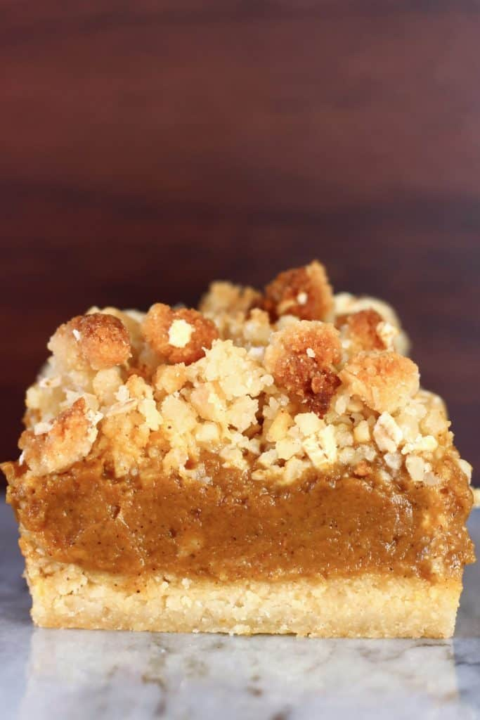 A vegan pumpkin pie bar with crumble topping against a brown background