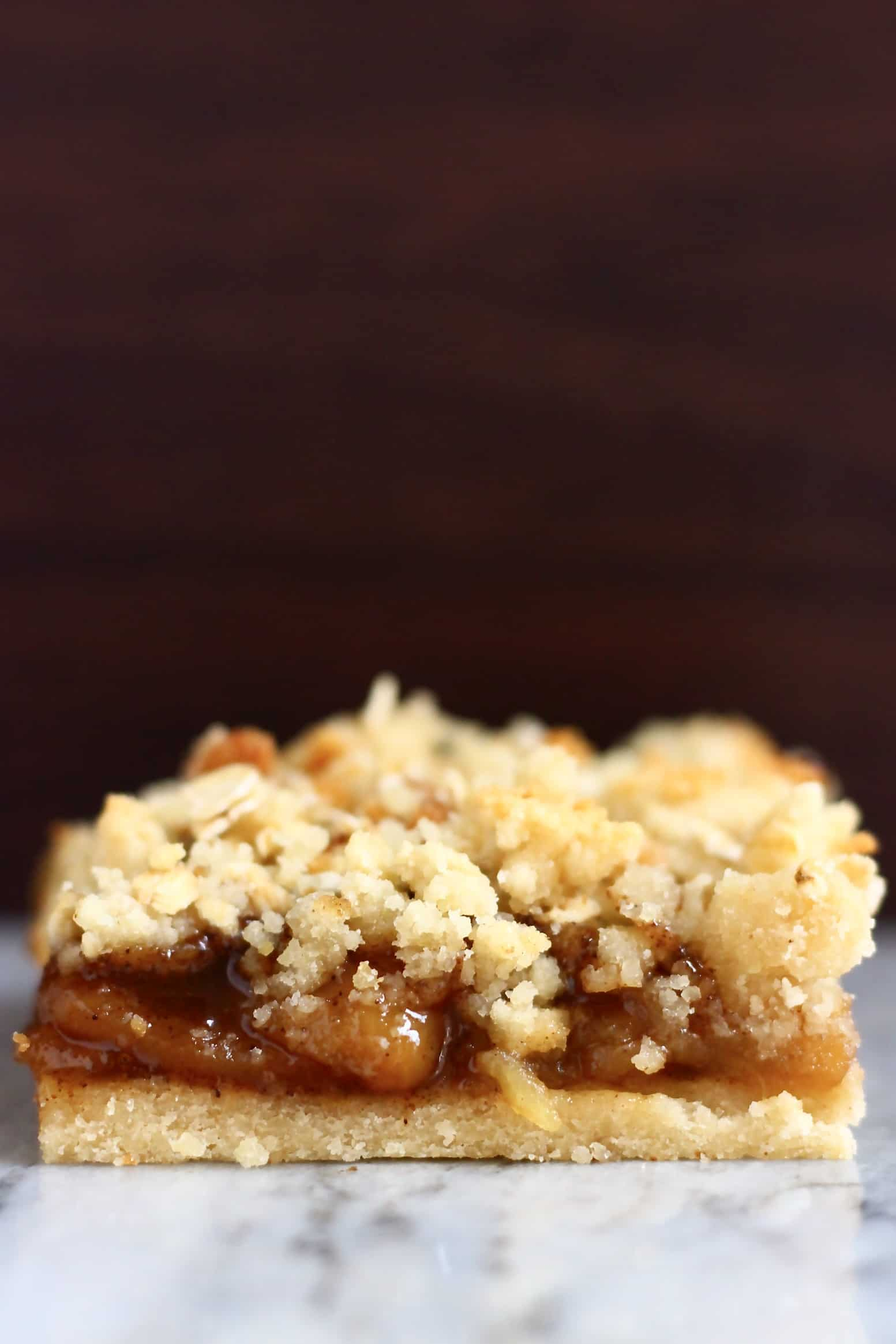 Apple pie bar on a marble slab against a dark brown background