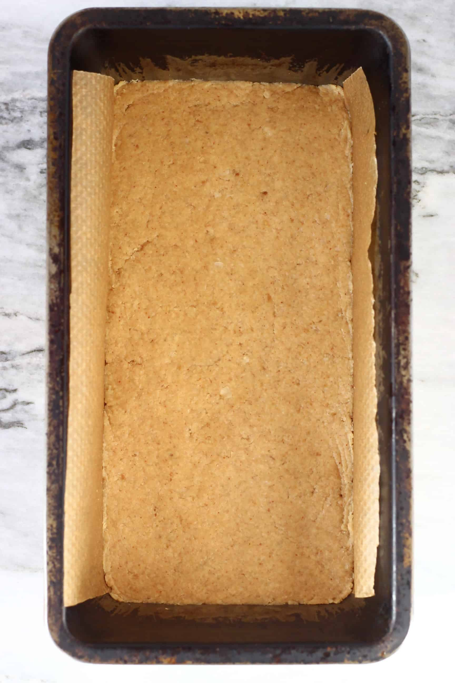 Peanut butter bar mixture in a loaf tin lined with baking paper