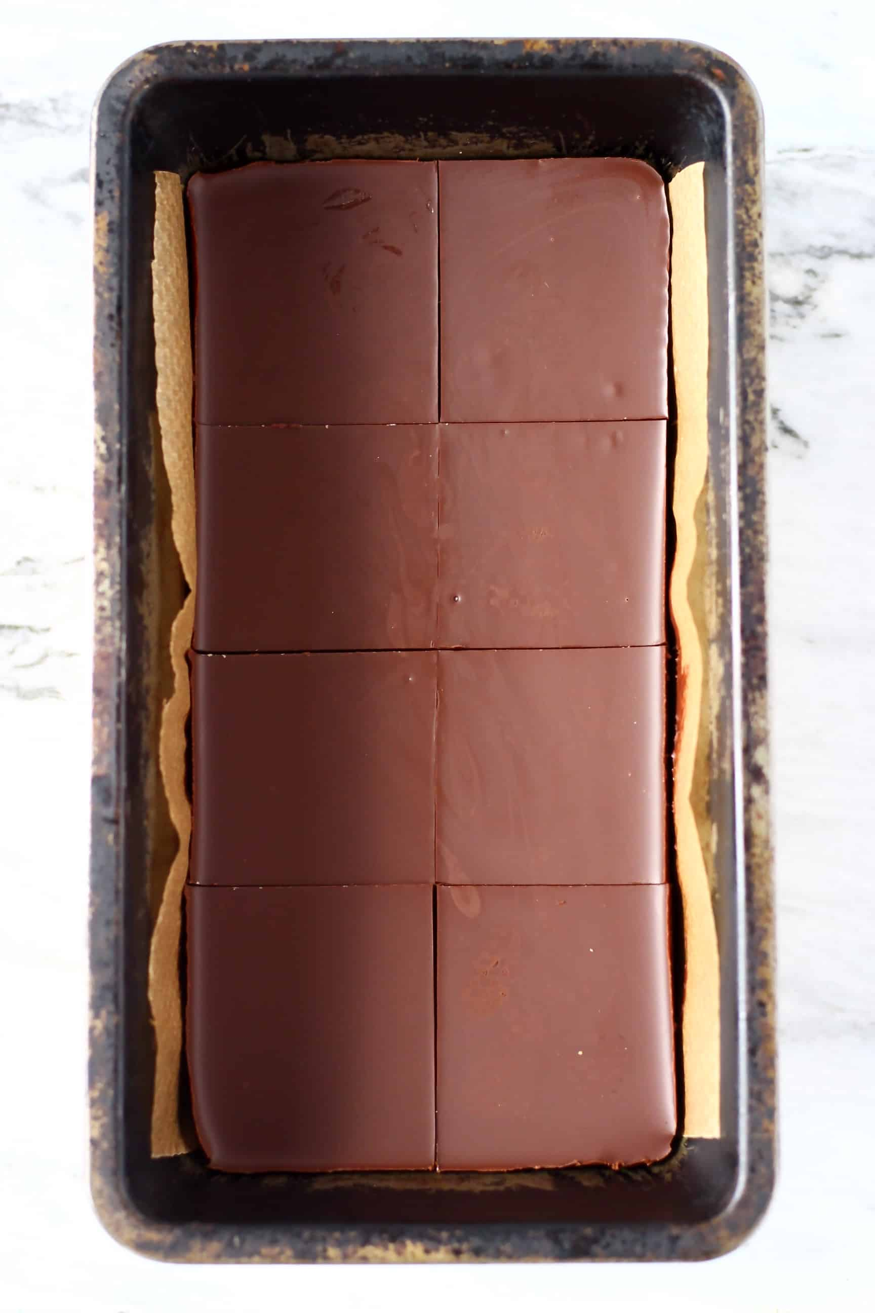 Chocolate peanut butter bars in a loaf tin cut into eight squares