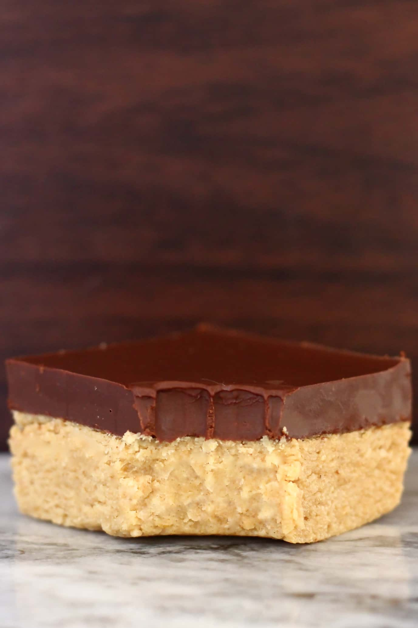 A vegan chocolate peanut butter bar topped with dark chocolate with a bite taken out of it