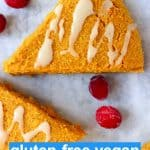 Three triangular pumpkin scones drizzled with white icing on a marble background