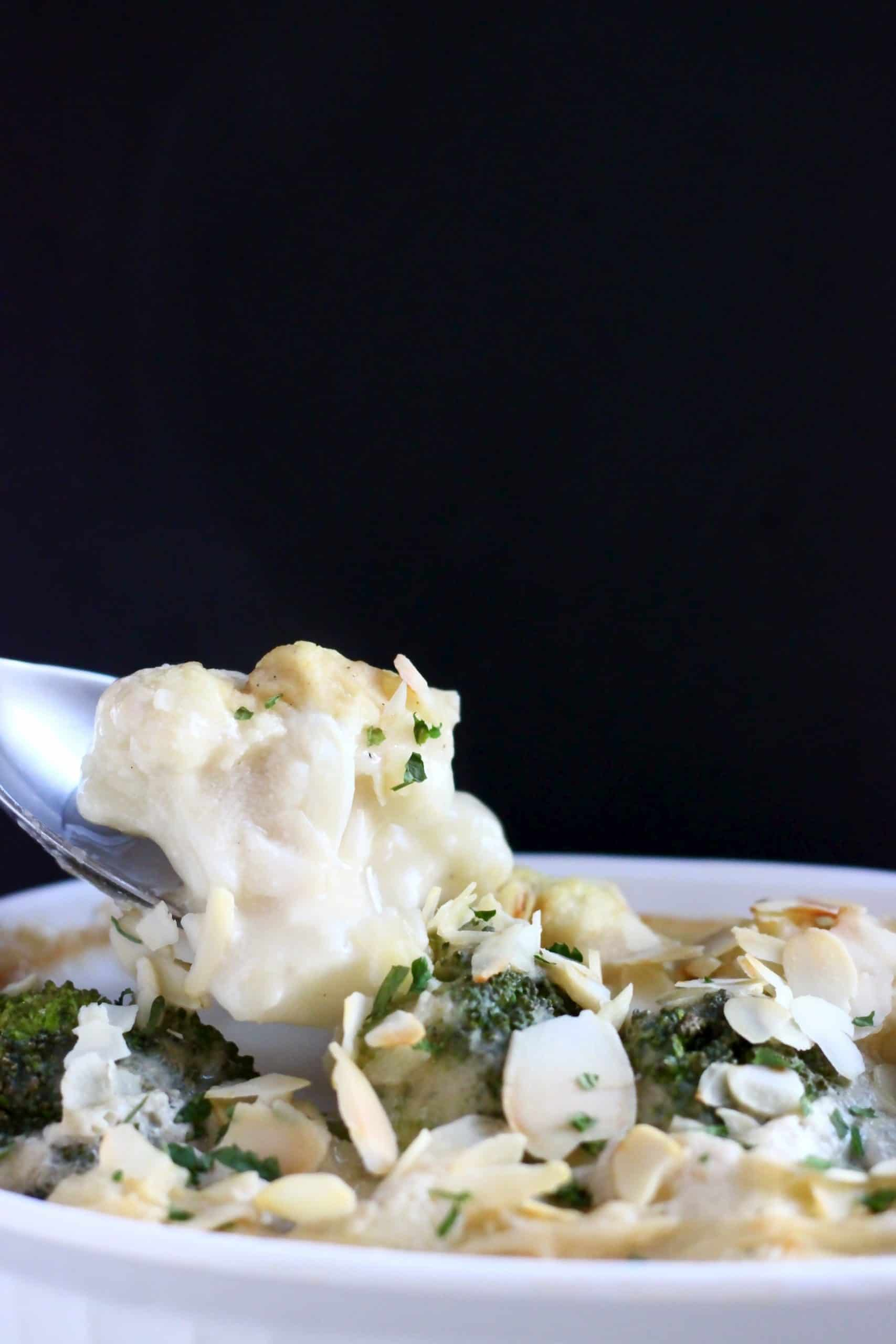 A spoon lifting up a mouthful of cauliflower cheese gratin