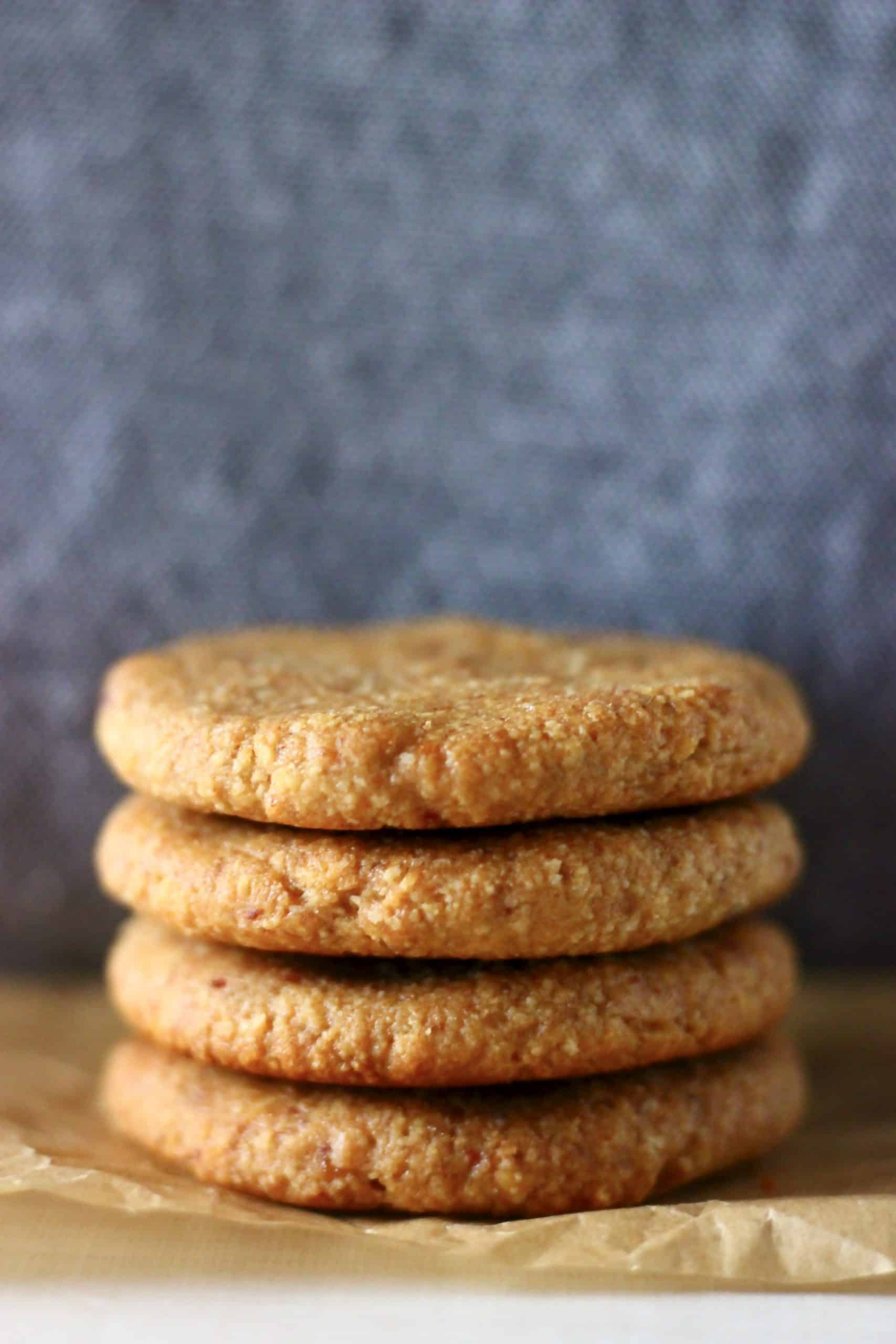 Four golden brown cookies stacked on top of each other on a sheet of brown baking paper