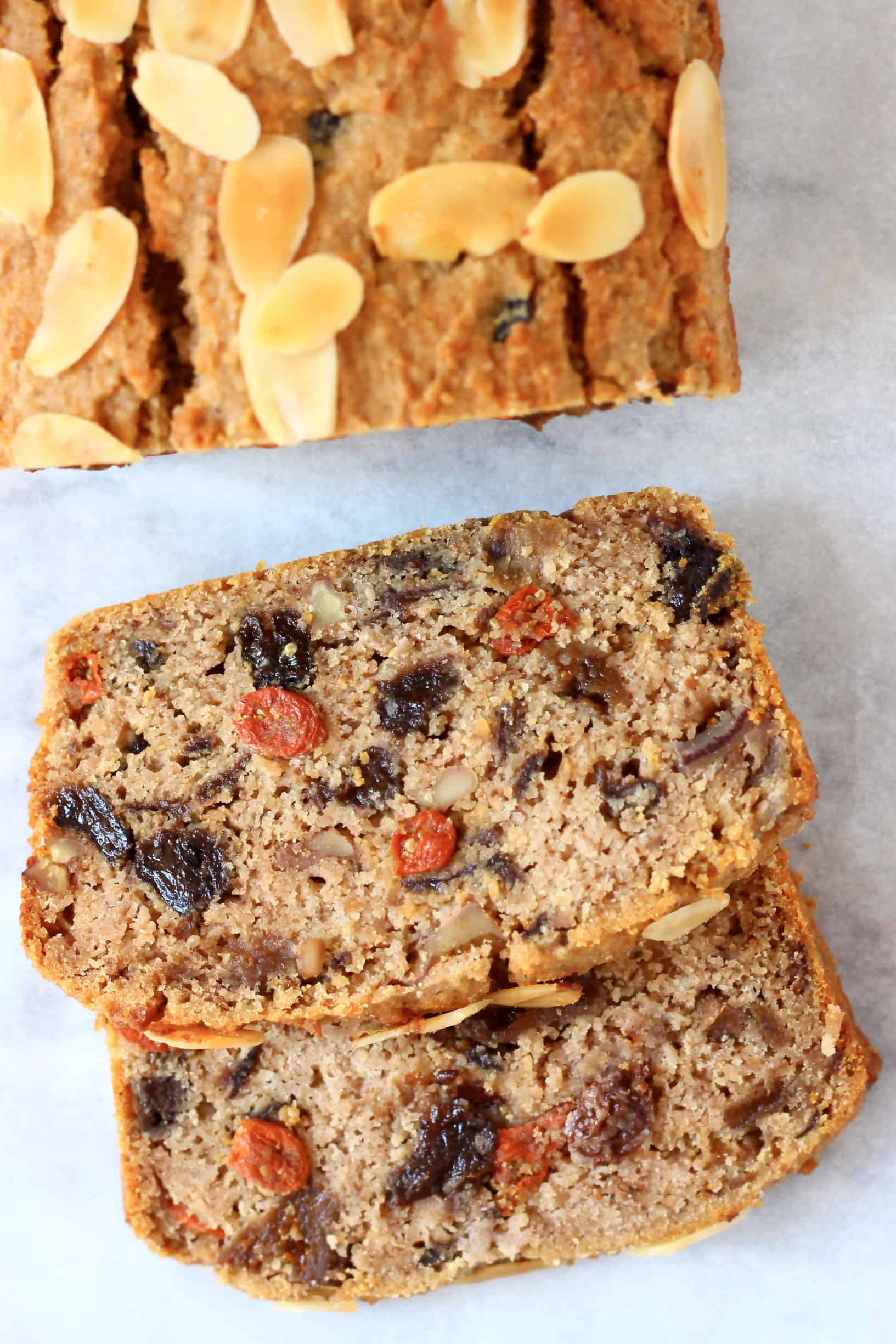 A gluten-free vegan fruit cake with two slices next to it