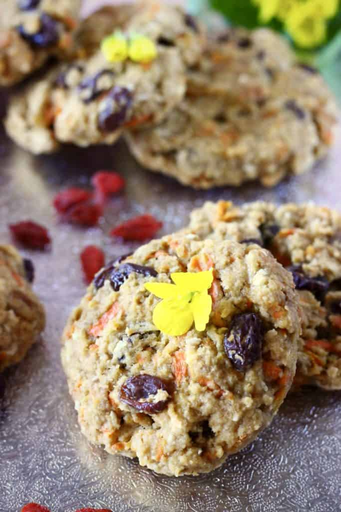 Five carrot cake cookies with raisins on a silver background