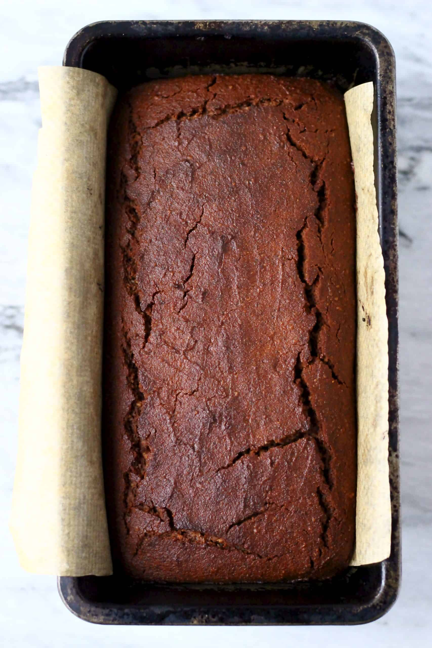 A gluten-free vegan gingerbread loaf cake in a loaf tin lined with baking paper