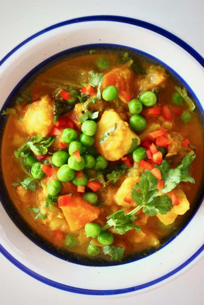 A potato and pea curry in a white bowl with a blue rim