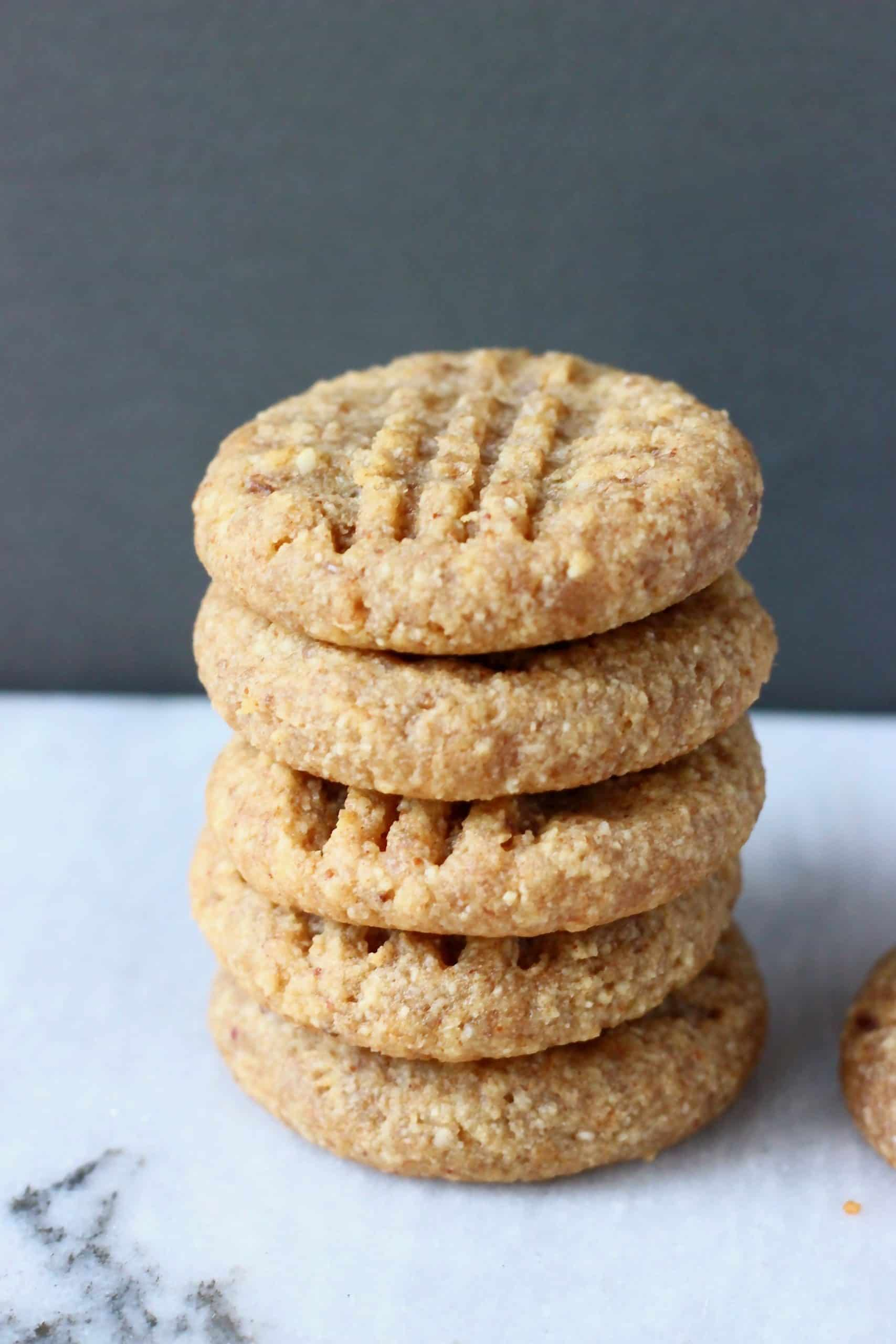 A stack of five peanut butter cookies on a marble slab against a grey background
