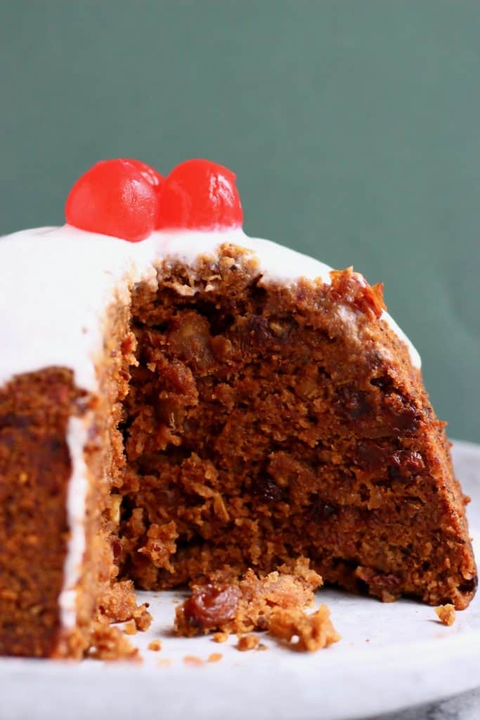Christmas pudding with a slice cut out of it topped with cherries