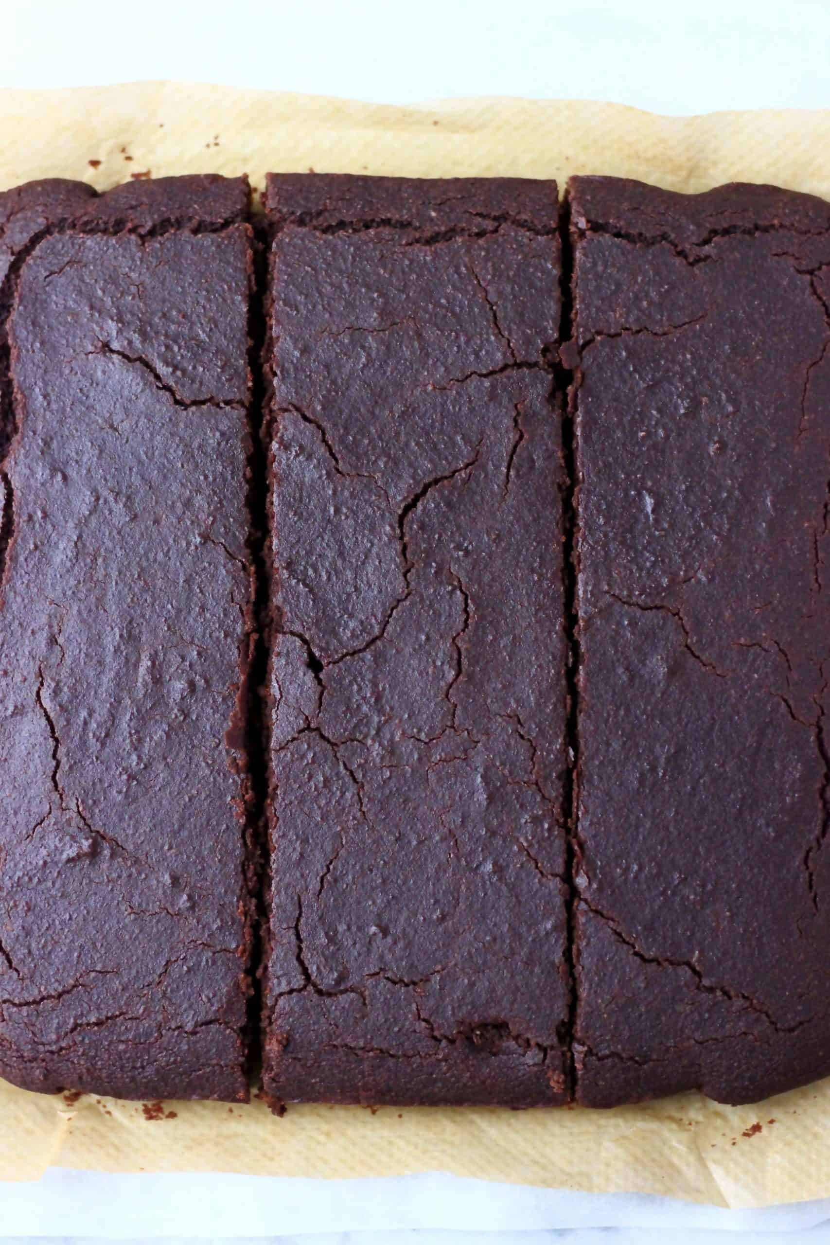 Square vegan chocolate sponge cake cut into three