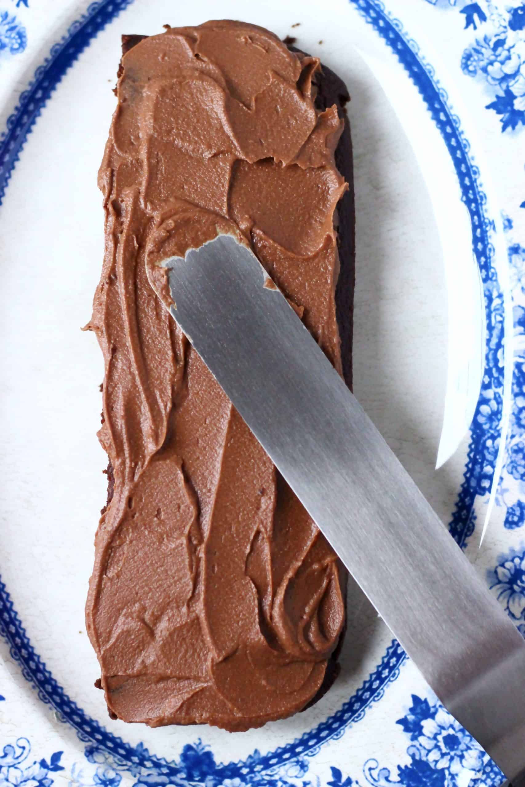 A rectangle of vegan chocolate cake with a palette knife spreading chocolate buttercream on top