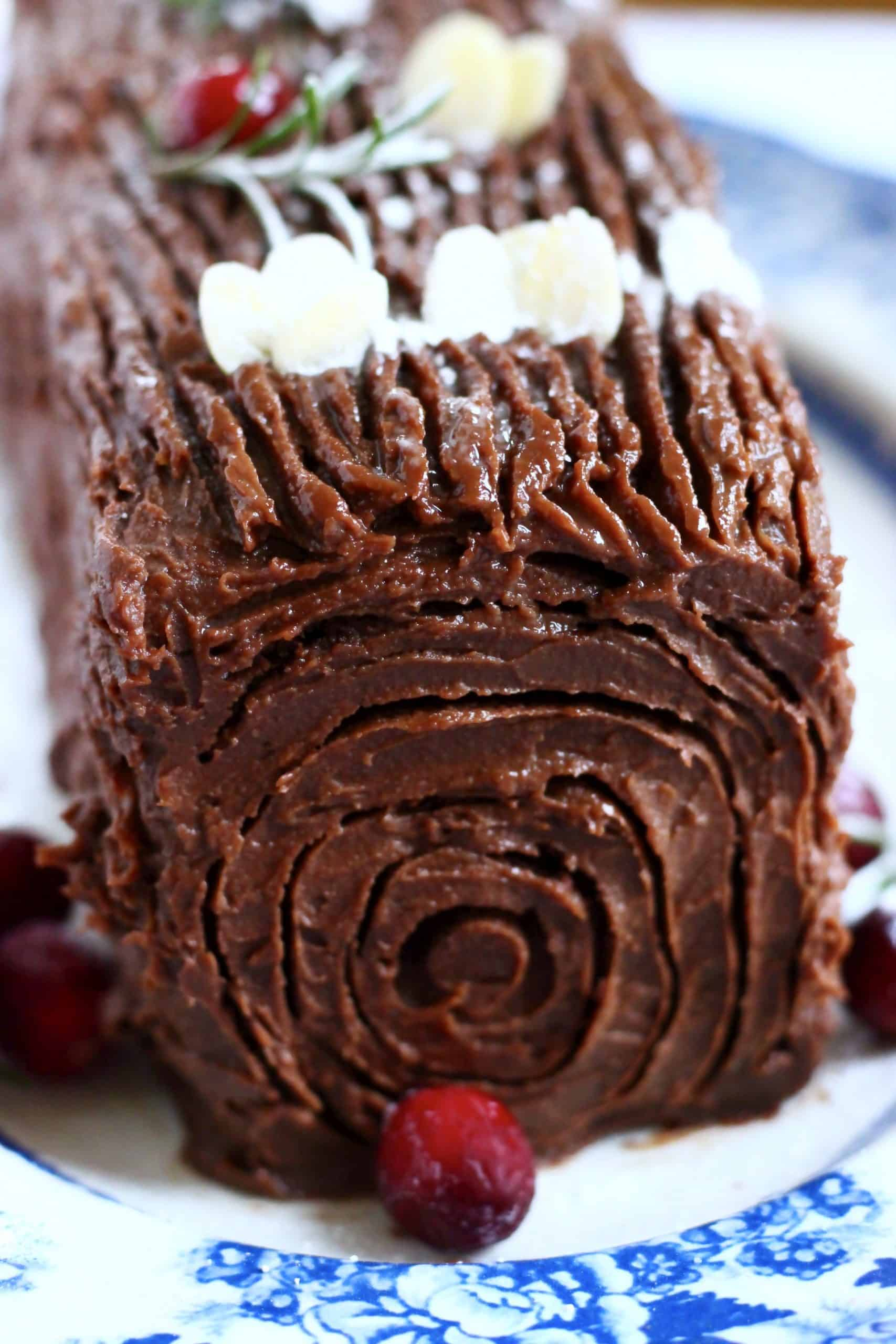 A gluten-free vegan yule log decorated with cranberries, rosemary and flaked almonds