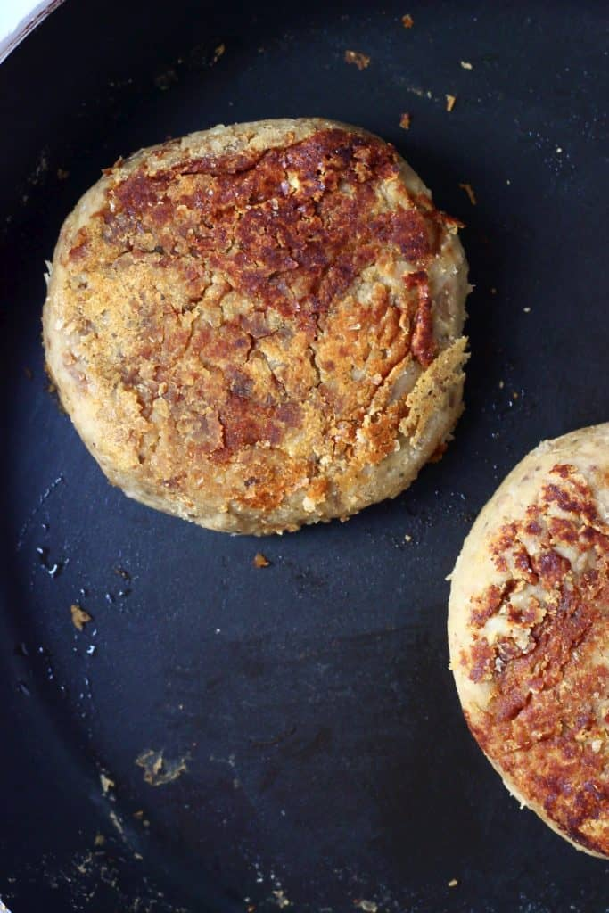Two golden brown vegan Christmas burger patties in a black frying pan