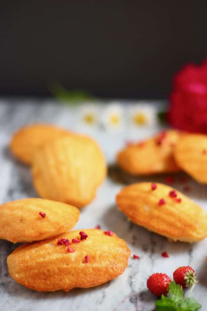 Seven madeleines on a marble background decorated with flowers