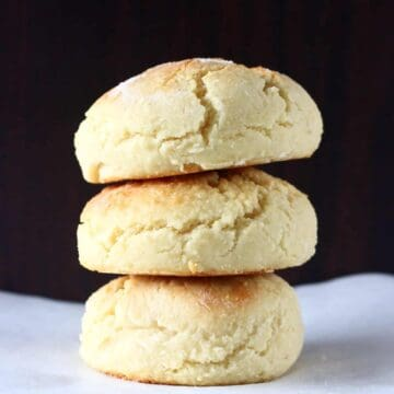 Three gluten-free vegan biscuits on top of each other against a dark brown background
