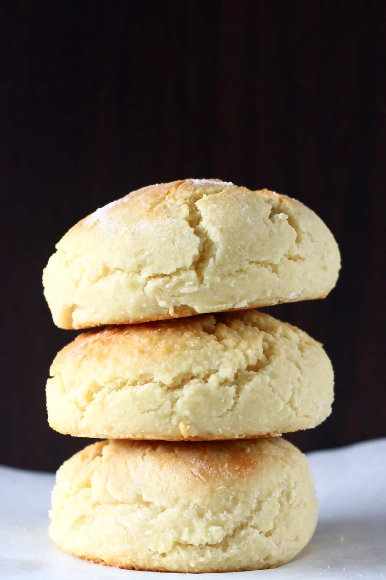 Three gluten-free vegan biscuits stacked on top of each other against a dark brown background