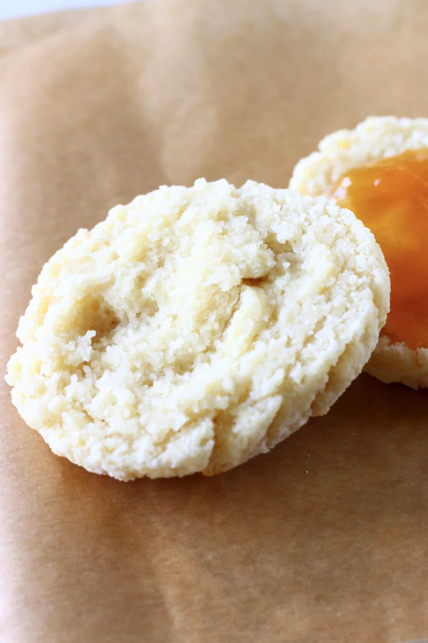 A halved gluten-free vegan biscuit with one half spread with apricot jam