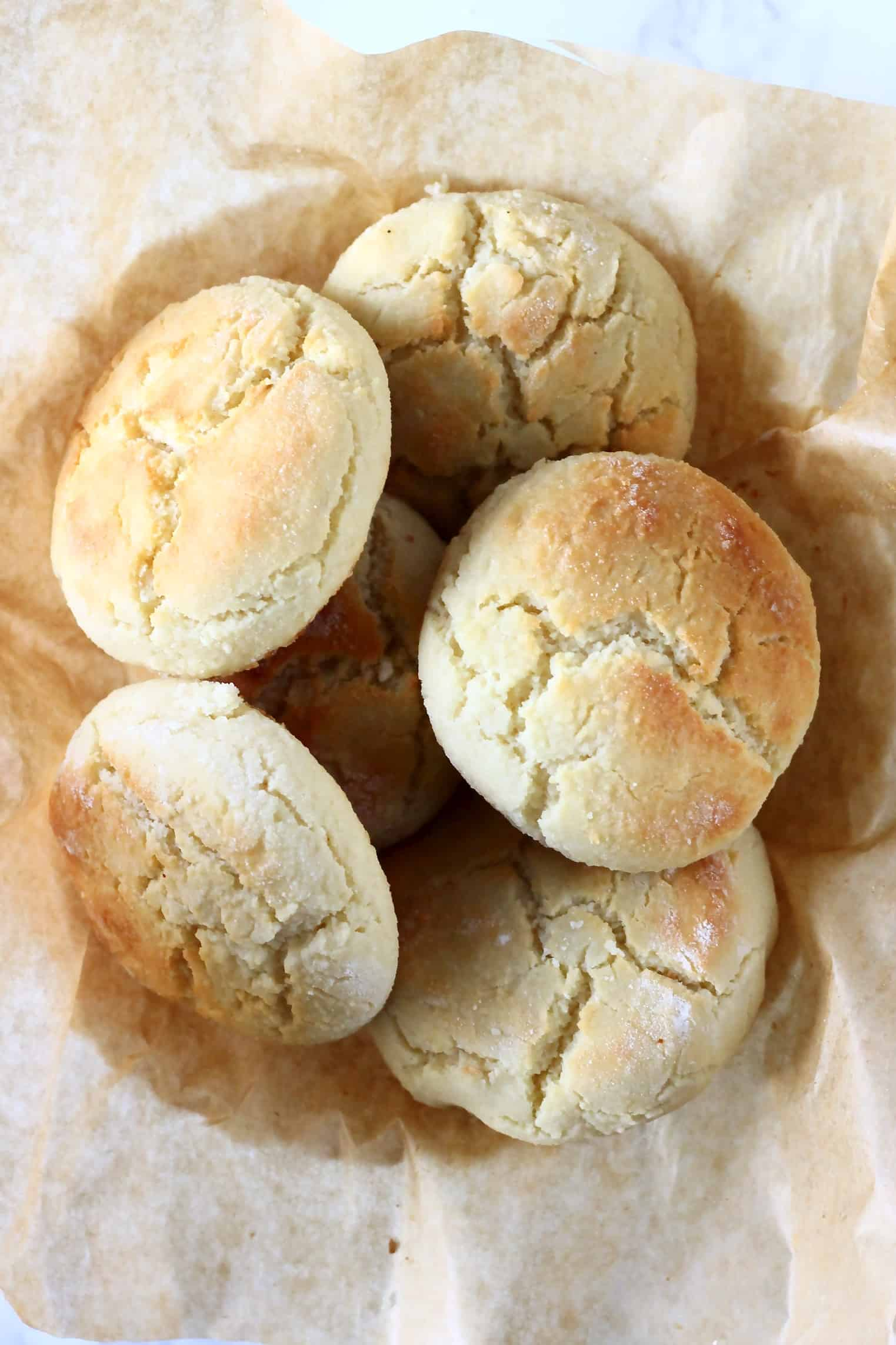 Six gluten-free vegan biscuits in a bowl lined with brown baking paper