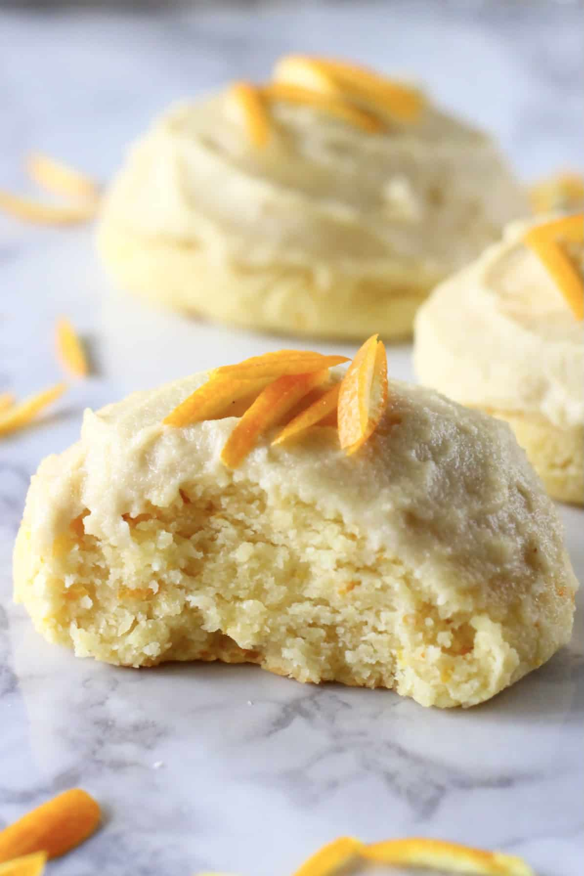 Three orange cookies with frosting and orange zest with a bite taken out of one