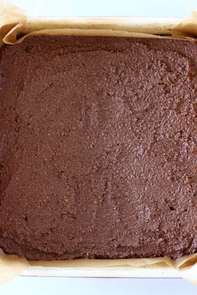 Raw brownie batter in a square baking tin