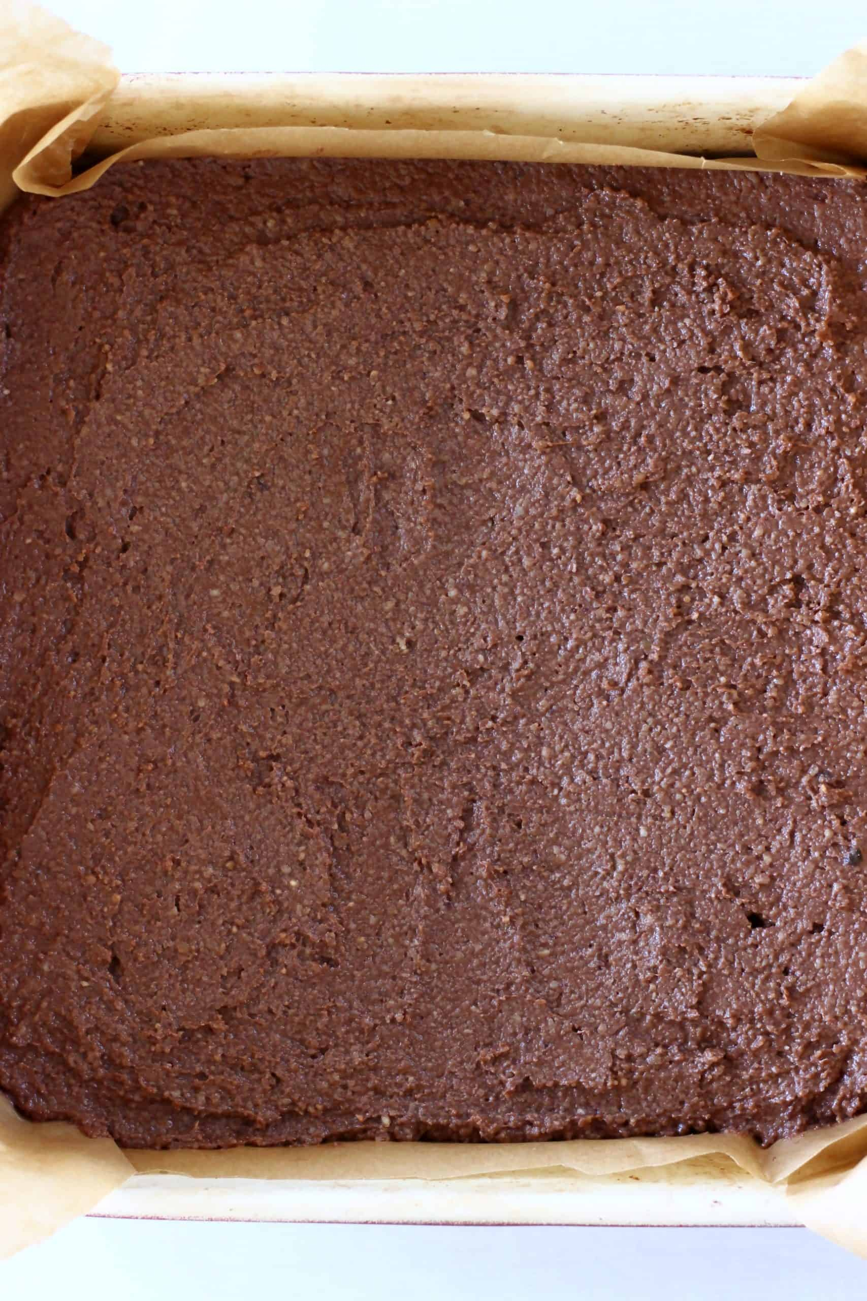Raw vegan peppermint brownie batter in a square baking tin lined with baking paper