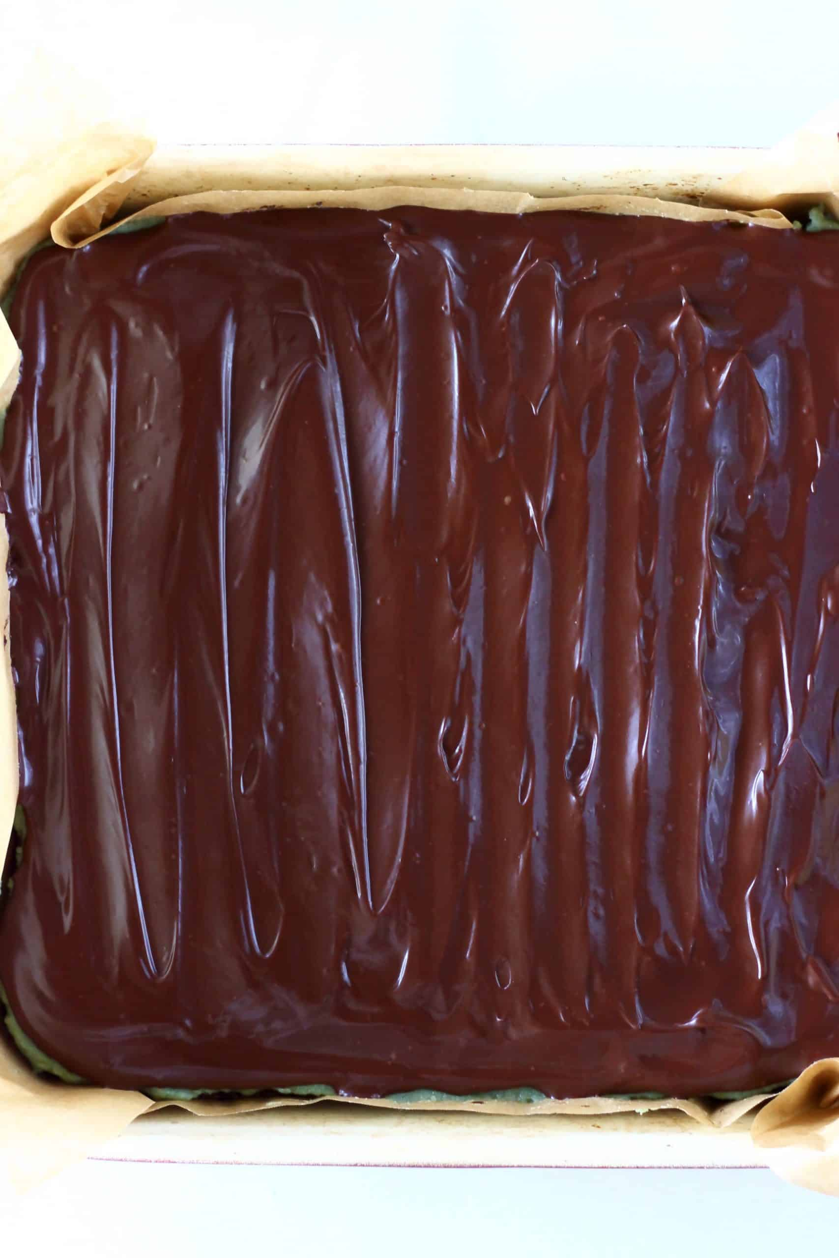 Vegan chocolate ganache spread over vegan peppermint brownies in a square baking tin lined with baking paper
