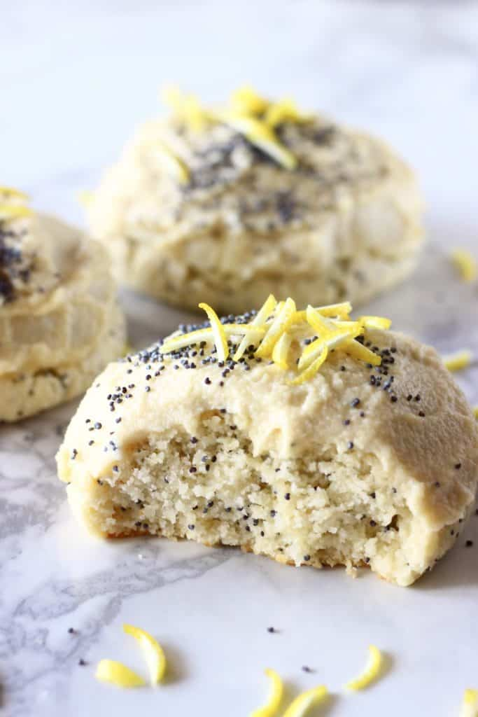 Lemon poppy seed cookies with frosting with a bite taken out of one