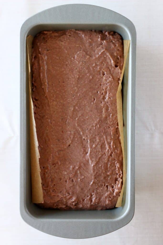 Raw gingerbread cake batter in a silver loaf tin