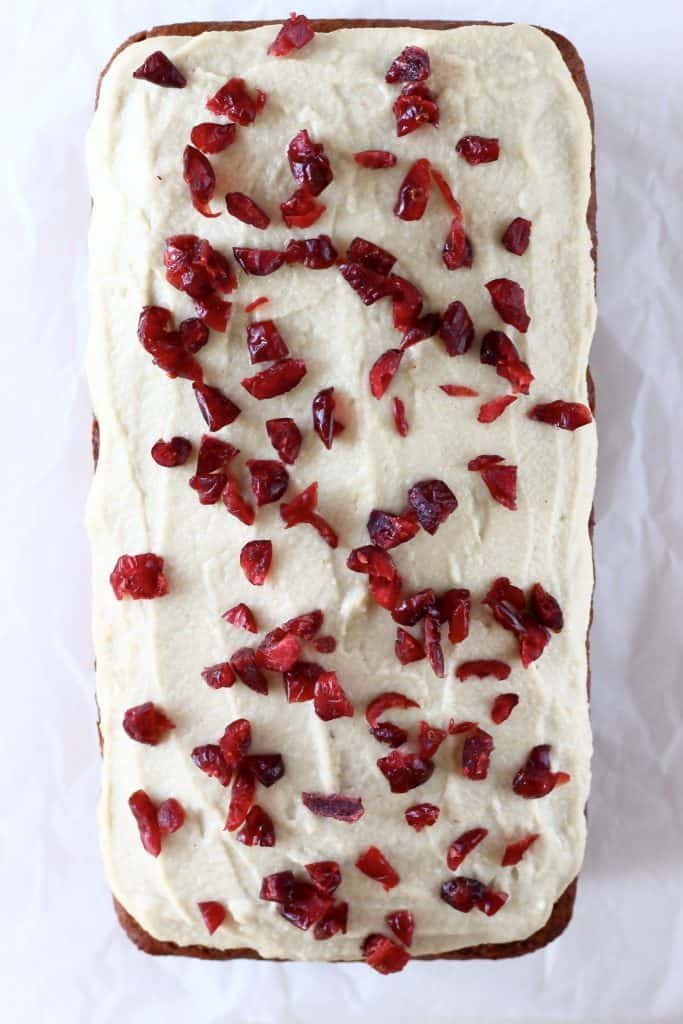 Gingerbread loaf cake with white frosting and dried cranberries on top