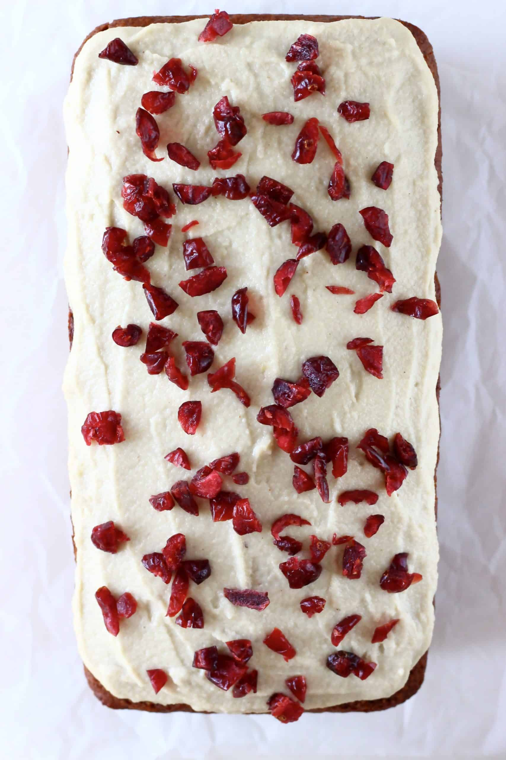 A gluten-free vegan gingerbread loaf cake with vegan cream cheese frosting and dried cranberries on top